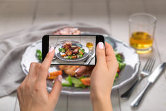 Photographing food concept - woman takes picture of hot meat dishes. Pork ribs grilled with salad and apples on a plate. Stock Photography