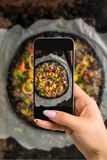 Photographing food concept - woman takes picture of italian pizza with black dough and seafood on a baking tray from the Royalty Free Stock Image