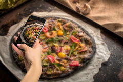 Photographing food concept - woman takes picture of italian pizza with black dough and seafood on a baking tray from the Stock Photo