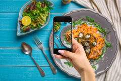 Free Photographing Food Concept - Woman Takes Picture Of Pasta With Eggplants, Tomato, Cheese, Arugula And Salad Stock Images - 98024184