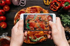 Photographing food. Hands taking picture of delicious pizza with smartphone.  Stock Photography