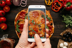 Photographing food. Hands taking picture of delisious pizza with smartphone.  Stock Photography
