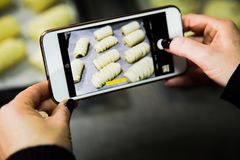 Photographing food with smartphone. Photographing food. Hands bread buns with smartphone stock photography