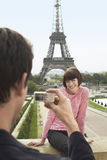 Photographing In Front Of Eiffel Tower. Cropped men photographing women in front of Eiffel Tower Royalty Free Stock Photos