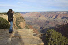 Photographing the Grand Canyon. A woman photographs the amazing scenery of the grand canyon Stock Photos