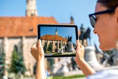 Photographing Michael's church in Cluj Napoca. Female tourist photographing with digital tabet Michael's church in Cluj Napoca. Traveling Romania Royalty Free Stock Photography