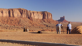 Photographing Monument Valley 2. An obese photographer with a wife ready to shade the camera and two children playing nearby is shooting Monument Valley (Navajo Stock Images