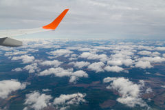 Photographing from a plane window. Flying a plane over the clouds Stock Photos