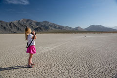 Photographing sailing rocks. 3 years old girl photographing sailing rocks at the Racetrack Playa. Death Valley, Nevada Stock Photo