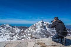 Photographing Shtirovnik peak. Tourist taking pictures of the stunning mountain winter landscape panorama of Stirovnik peak, the highest summit of the Lovcen stock photos