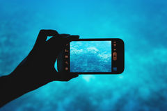Photographing with a smartphone in the red sea Royalty Free Stock Image