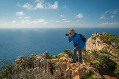 Photographing stunning Shipwreck Cove. Female tourist standing on the edge of a cliff and photographing the stunning cliffs in Shipwreck Cove in summer on Zante stock image