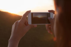 photographing sunset with Smart phone camera Royalty Free Stock Photos