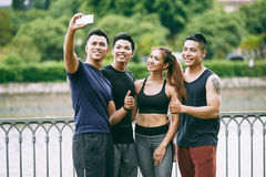 Photographing together. Cheerful Asian young people photographing together after training Stock Photography