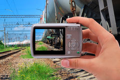 Photographing train. Digital camera in hand of photographing train Stock Photos