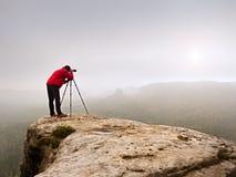 Photographr die beeldzoeker van tribune van de dslr de digitale camera op driepoot onderzoeken Kunstenaar die berg en bewolkt lan Royalty-vrije Stock Foto's