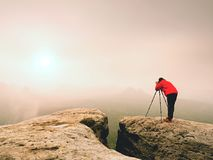 Photographr looking into viewfinder of dslr digital camera stand on tripod. Artist  photographing mountain and cloudy landscape. Man check picture on screen Stock Photos