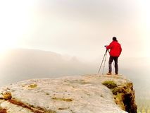Photographr looking into viewfinder of dslr digital camera stand on tripod. Artist  photographing mountain and cloudy landscape. Man check picture on screen Stock Image