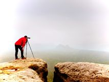 Photographr looking into viewfinder of dslr digital camera stand on tripod. Artist  photographing mountain and cloudy landscape. Man check picture on screen Royalty Free Stock Photos