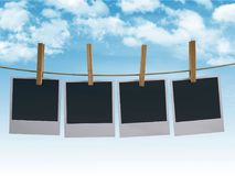Photographs hanging on a clothesline. Blank photographs hanging on a clothesline with sky background, 3d illustration Stock Photos