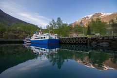 Photography of a blue cruise with small hill with beautiful water reflection Royalty Free Stock Photos