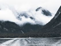 Photography of Body of Water Surrounded by Mountains and Fogs royalty free stock image