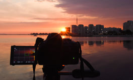 Photography camera while taking beautiful cloudy sunset scene. Stock Photo