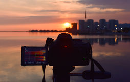Photography camera while taking beautiful cloudy sunset scene. Royalty Free Stock Photography