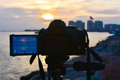 Photography camera while taking beautiful cloudy sunset scene. Royalty Free Stock Images
