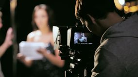 Photography director looks at camera screen against director and TV presenter. KAZAN, TATARSTAN RUSSIA - MAY 14 2018: Photography director looks at camera screen stock footage