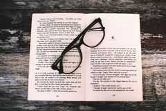 Photography of Eyeglasses on Top of Book Royalty Free Stock Photo