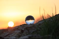 Photography of Glass Ball on Brown Rock Formation during Sunset Stock Image