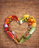 Photography of heart made from different fruits on wooden table. Heart symbol, diet concept. Healthy food photography of heart made from different fruits on Stock Images