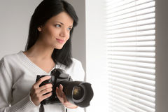 Photography is her hobby. Portrait of beautiful young woman hold. Ing a camera and looking through the window Royalty Free Stock Image