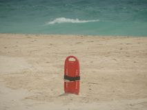 Red Lifesaver lifeguard in sand at beach. Photography horizontal lifeguard sand beach coast sun waves bay watch Lifesaver Royalty Free Stock Image