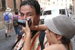 Photography lessons. A father learning his daughter to take proper photos on the streets of Rome, Italy Stock Photography