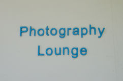 Photography lounge sign on white wall Royalty Free Stock Images