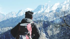 Photography of Man in Black Hooded Jacket and Red Backpack Facing Snow Covered Mountain Royalty Free Stock Photos
