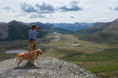 Photography man and his dog admire the mountain scenery Stock Photography