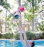 Photography of Man on Swimming Pool Tossing Toddler Above Pool stock image