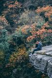 Photography of Man Wearing Black Hoodie With Black Pants Sitting on Stone Cliff Above Green and Red Leaved Forest Royalty Free Stock Photography