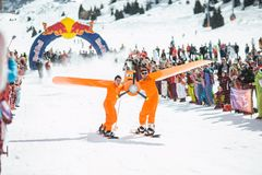 Photography of Men in Orange Suits Ridding Snowboard stock image