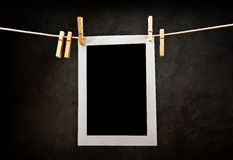 Photography paper attached to rope with clothes pins. Royalty Free Stock Image