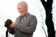 Exuberant senior man adjusting camera. Photography in park. Low angle of enthusiastic senior man laughing and using camera Royalty Free Stock Photos