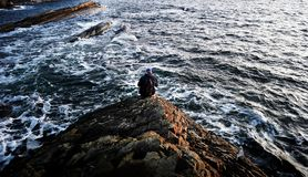Photography of Person Sitting on Rock Near Ocean Royalty Free Stock Photography