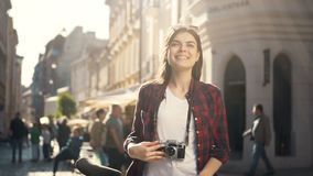 Photography with retro camera. Attractive long-haired brunette taking photos with retro camera in the sunlight, improving photography skills as riding a bike in stock footage