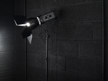 Photography studio light against a black brick wal Royalty Free Stock Image
