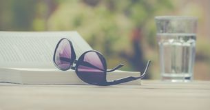 Photography of Sunglasses Near Book Stock Photos