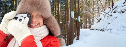 Happy woman with film camera over winter forest stock images