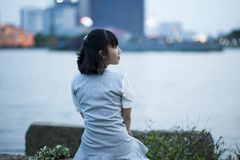 Photography of A Woman Sitting Beside Body of Water Royalty Free Stock Image